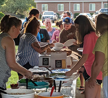 A group of people getting food at a potluck